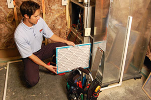 Mister Quik heating system technician consulting with home owner on maintenance needs